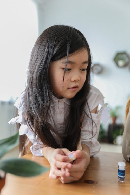 Adorable curious little Asian girl with long dark hair leaning on wooden table and looking away during lesson at school