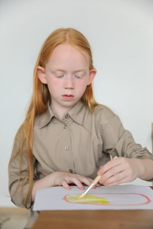 Serious redhead kid drawing with paintbrush and aquarelle on paper