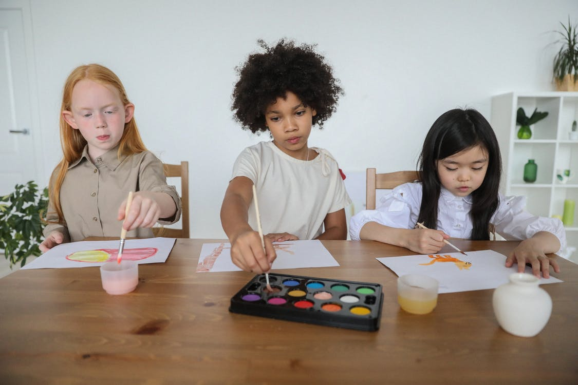 Talented diverse little girls painting on papers with watercolors while sitting together at table