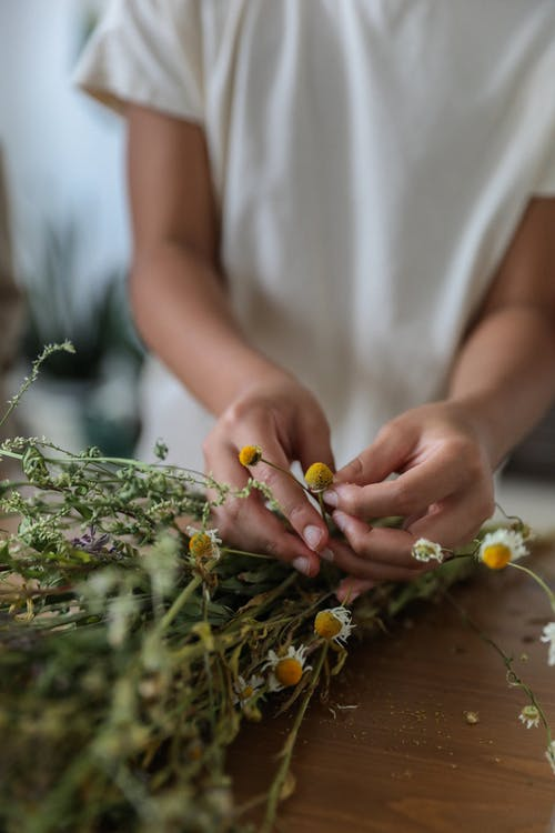 Faceless lady making delicate bouquet of tender wildflowers