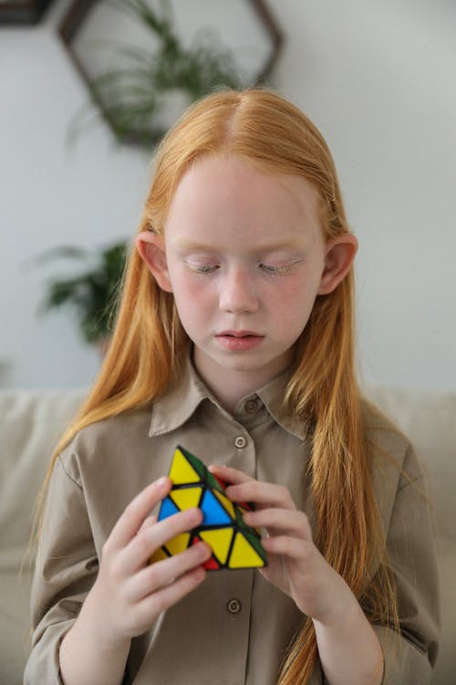 Smart concentrated little girl with long ginger hair playing with pyramid shaped 3D combination puzzle sitting on sofa at home