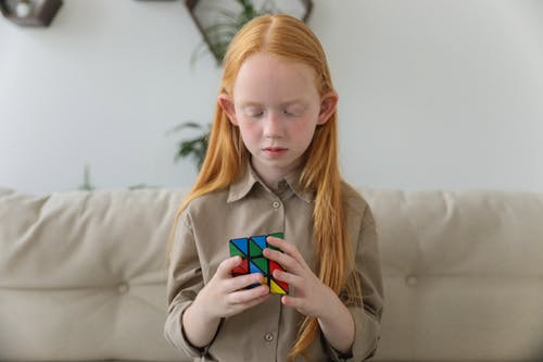 Cute girl thinking over bright puzzle cube