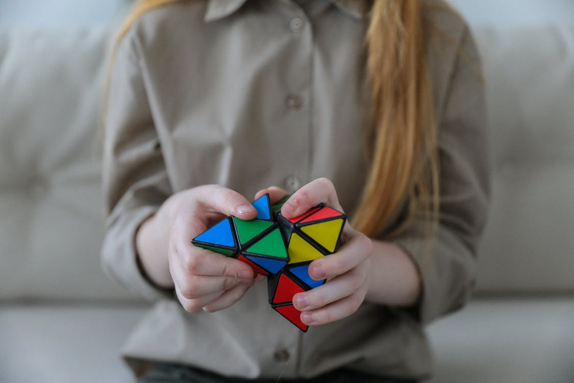 Crop anonymous girl demonstrating and solving colorful puzzle with triangles in soft focus