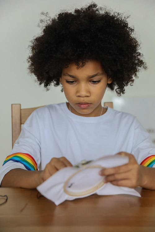 Cute serious diligent African American girl with curly hair embroidering on fabric with needle at table