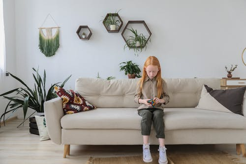 Serious girl in fashionable clothes solving puzzle and sitting on cozy sofa with bright cushion in contemporary lounge