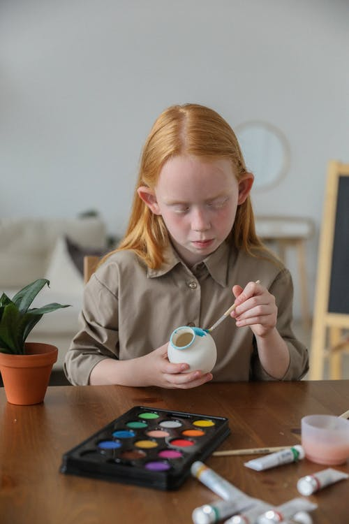 Focused cute girl decorating vase with watercolor