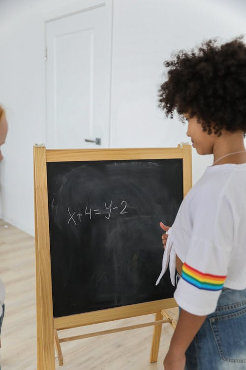 Back view of African American girl writing numbers and symbols on chalkboard in classroom