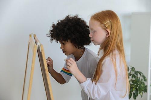 Kalme Multiraciale Meisjes Schilderen Op Ezel Schoolbord