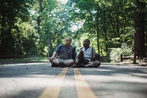 Pensive diverse hikers with backpacks sitting on asphalt roadway in countryside and looking away