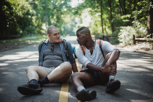 Gay couple resting on road