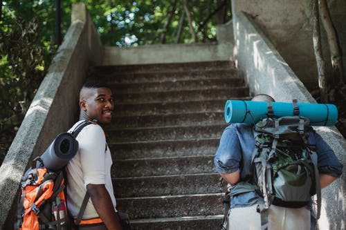Friends in casual clothes with backpacks with hiking equipment going upstairs in green park in daytime