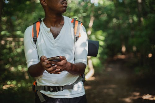 Crop unrecognizable African American man with backpack and smartphone searching route while going astray in green forest