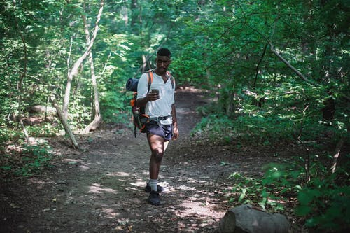 African American man with backpack in forest