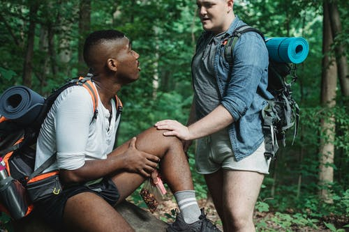 Multiracial men resting in forest during hiking
