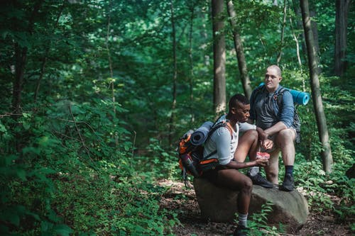 Multiethnic friends resting on stone during hiking