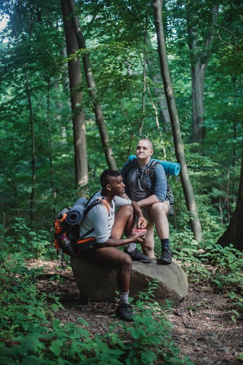 Full body of multiethnic men with backpacks relaxing on stone while having break for snack in forest