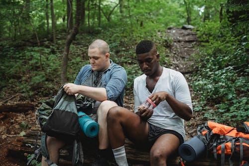 Multiracial men eating snack during hiking