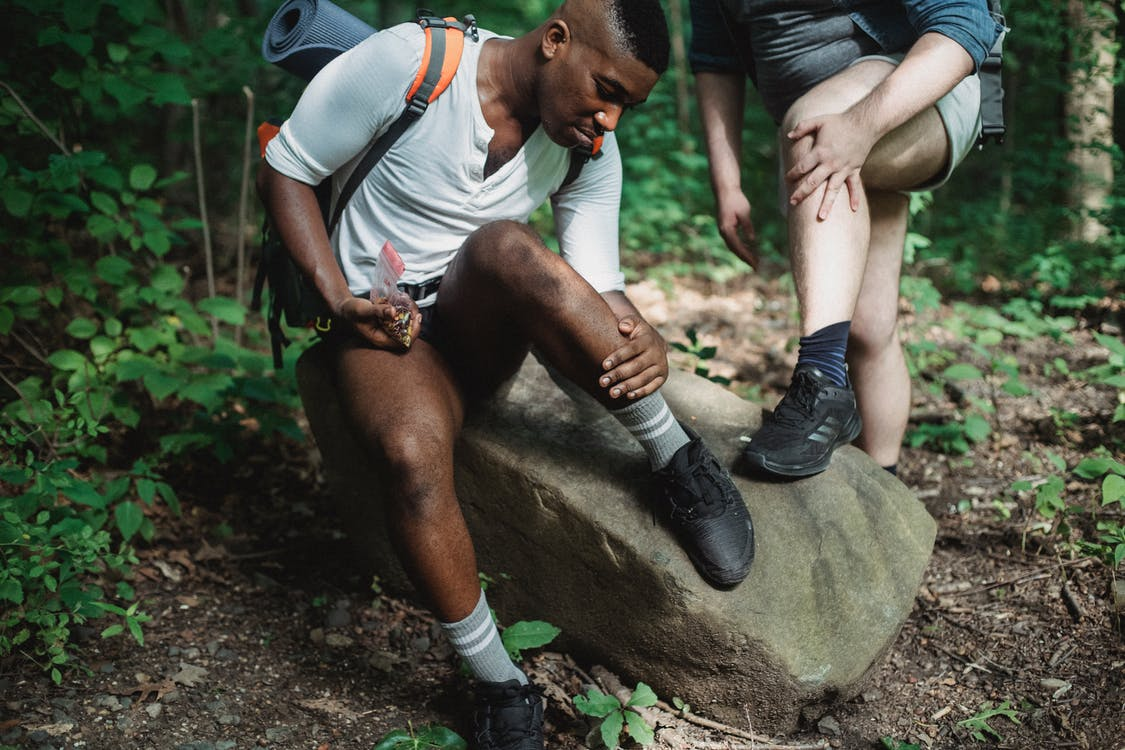 Multiethnic men in sportswear with backpacks resting together and searching for ticks on legs in green lush forest during trek