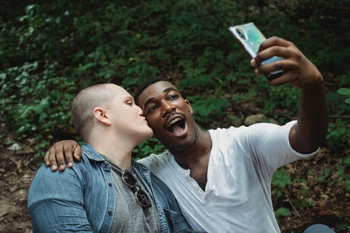 Young lgbt couple taking selfie in forest