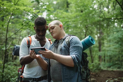 Multiracial friends using navigator on smartphone in forest