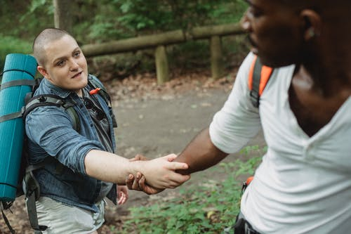 Unrecognizable black adventurer providing hand for happy plump male friend with big backpack and rolled rug in woodland in daytime
