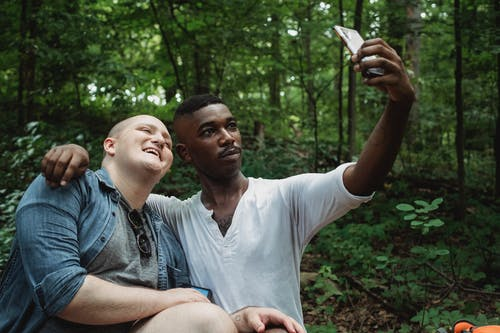 Gay couple hugging and taking selfie in forest