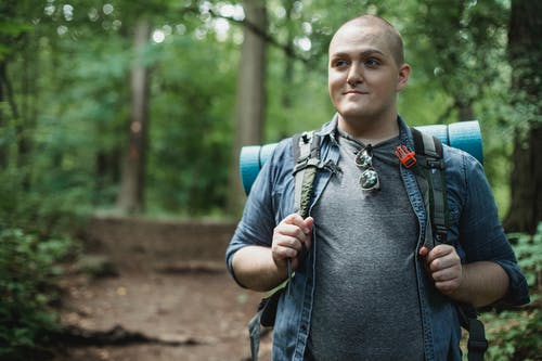 Smiling plus size male backpacker standing on path in green dense forest during hiking