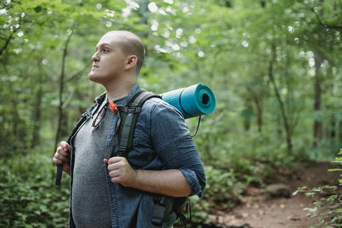 Male plump backpacker with hiking equipment in woods