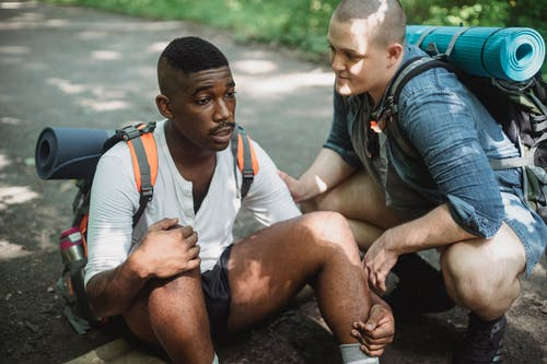 Black man resting on ground during hike with friend