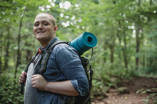 Positive backpacker exploring nature in forest