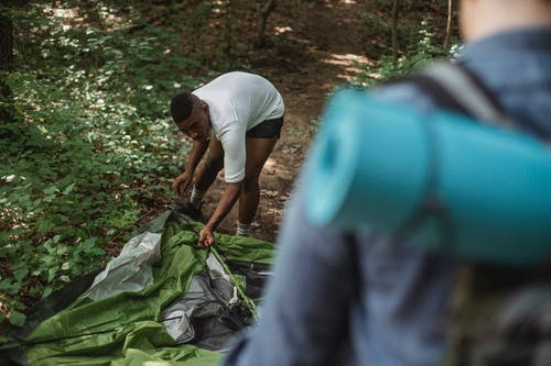 Male African American backpacker putting up tent in forest
