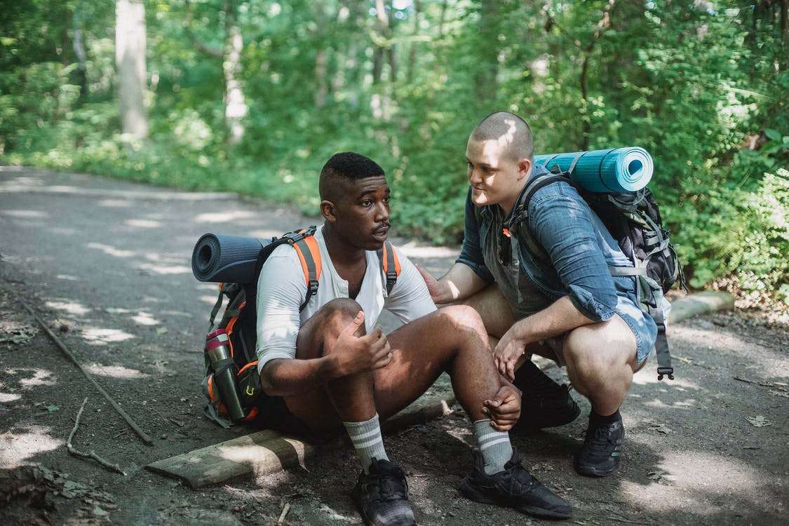 Black exhausted tourist resting on ground with friend