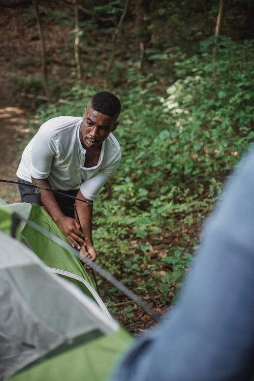 Black man putting tent in forest