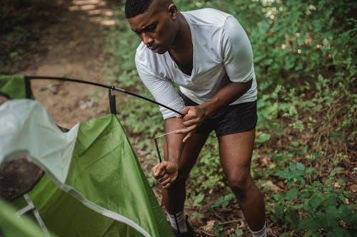 严重的黑人旅行者试图在森林里建立帐篷