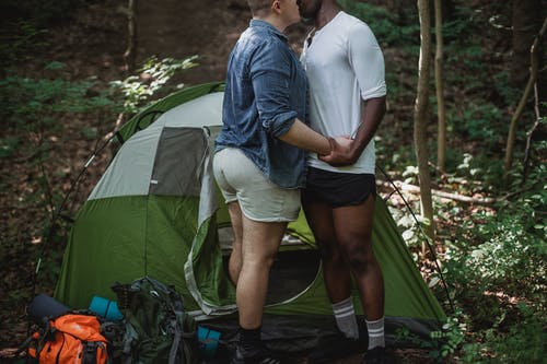Happy gay couple kissing near tent in forest