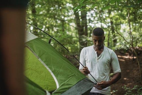 Homme Noir Réfléchi Debout Dans La Forêt Et La Mise En Place De La Tente
