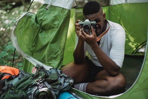 Black man taking photo on vintage camera in nature