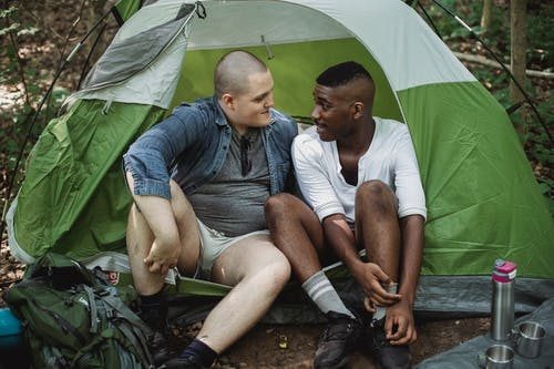 Male diverse friends resting in tent in forest