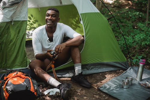 Full body of cheerful African American male traveler enjoying travelling while sitting in tent in woods