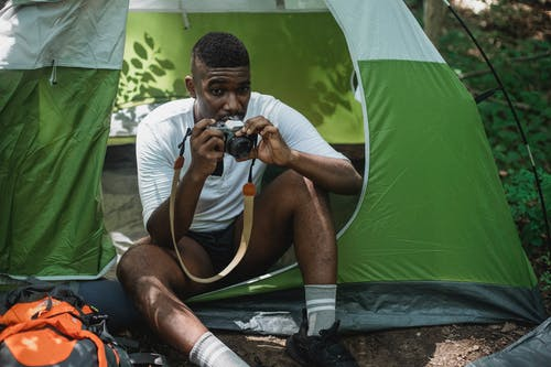 Serious African American tourist resting in tent while using old photo camera in green woods