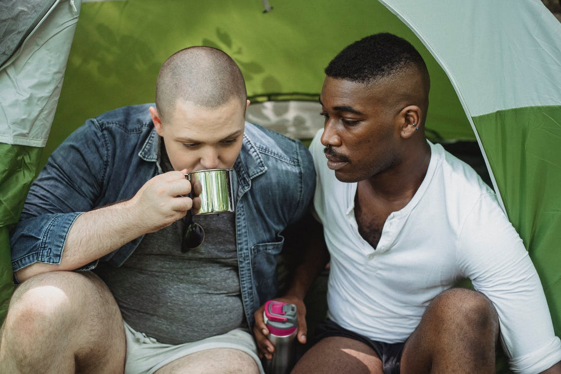 Man drinking tea from thermos sitting with black friend