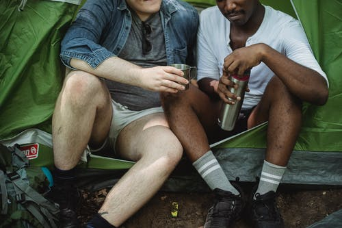 Diverse friends having rest in tent with tea in thermos