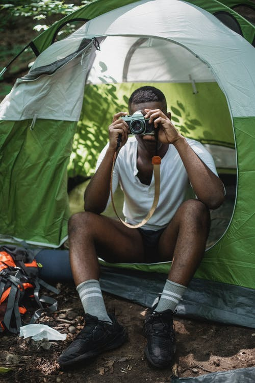 Full body of African American camper sitting in tent and taking picture on retro photo camera while traveling across nature