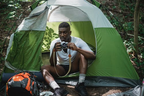 Serious African American male tourist sitting in camping tent with vintage photo camera while hiking in forest