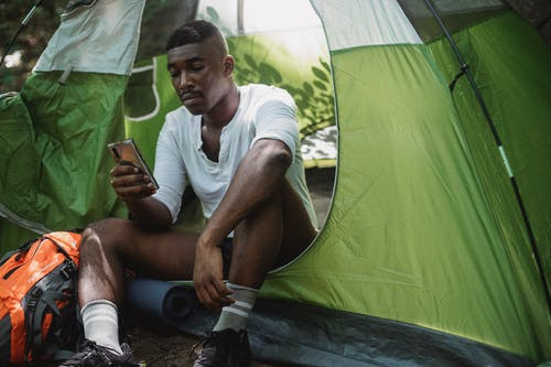Unhappy black man surfing smartphone in tent