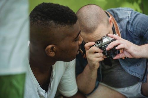 黒人の友人とハイキングしながらカメラで写真を撮る男