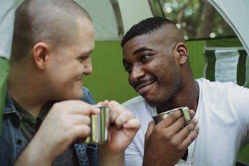 Positive multiethnic same sex couple drinking tea in tent