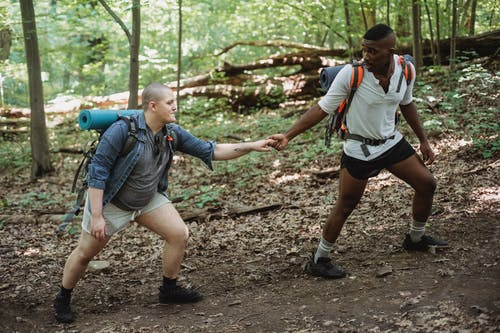 Active diverse same sex having hike in forest