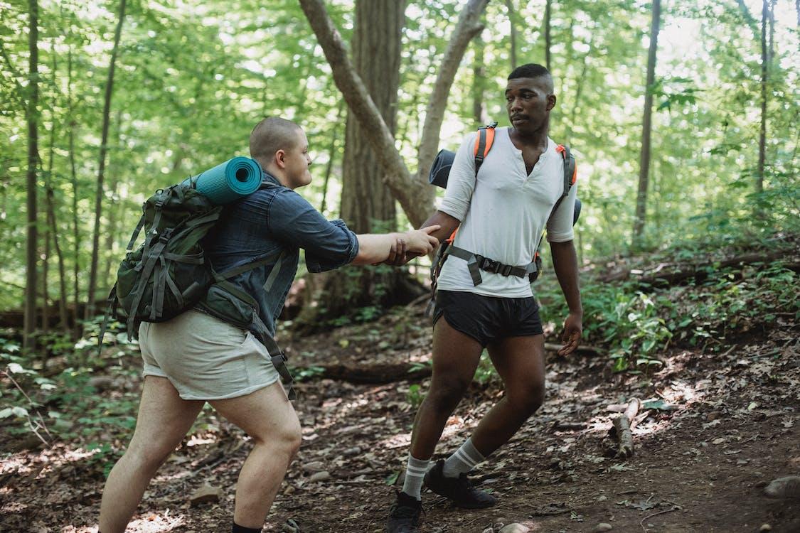 Strong black man helping friend to climb up