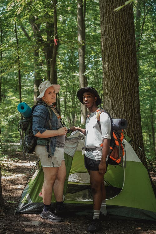 Friends standing near camping tent in forest on summer day